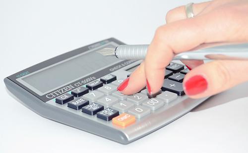 Женские пальцы печатают на калькуляторе