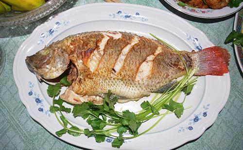 Рыба с зеленью на тарелке