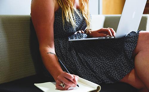 Девушка что-то переписывает с монитора ноутбука