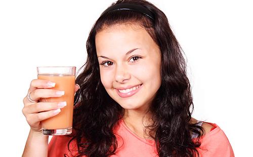 Девушка с сияющей улыбкой держит стакан с морковным фрешем