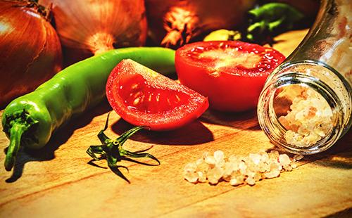 Перец и разрезанный помидор на столе