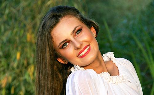Ослепительная улыбка девушки в белой блузке