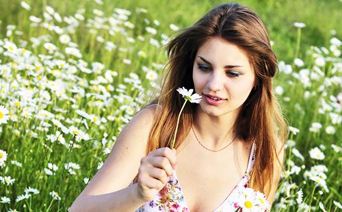 Девушка с ромашкой на летнем поле